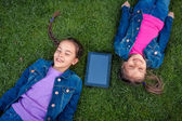 Smiling girls lying on grass with digital tablet — Stock Photo