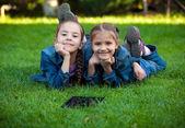 Portrait of two little girls lying on grass with tablet — Zdjęcie stockowe