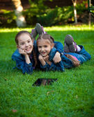 Two girls having fun on grass with tablet — Stock Photo