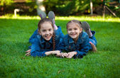 Smiling girls using tablet while lying on grass at yard — Stock Photo