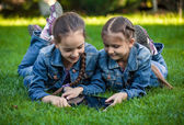 Two twin girls using tablet at park — Stock Photo