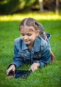 Shot of little girl lying on grass with tablet — Stock Photo