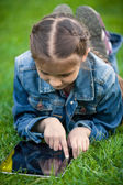 Small girl lying on grass and pointing at touchscreen — Zdjęcie stockowe
