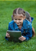 Small girl lying on grass and reading book from tablet — Stock Photo