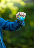 Ittle girl squeezing Earth globe at hand — Stock Photo