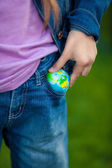 Conceptual photo of girl putting globe in pocket — Stock Photo