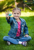 Smiling girl sitting on grass and holding Earth ball at hand — Foto Stock