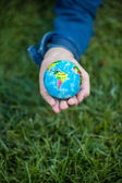 Girl holding small Earth globe in hand against grass background — Stock Photo