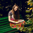 Brunette girl reading book on bench at park — Stock Photo #50784081