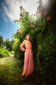 Slim woman in long dress posing at flowering bushes at park — Stock Photo