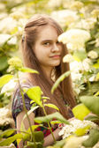 Photo of beautiful brunette girl posing at flowering bushes — Stock Photo