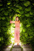 Romantic woman posing at floral arch at garden — Stock Photo