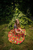 Woman in colorful skirt sitting on grass next to bushes — Stock Photo