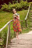 Young country girl smelling field flowers on wooden bridge — Stock Photo