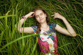 Portrait of beautiful cute girl sleeping in high grass — Stock Photo