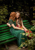 Redhead woman kissing brunette girl on bench at park — Stock Photo