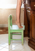 Little girl standing on tiptoes on chair at bathroom — Foto de Stock