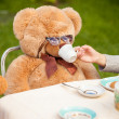 Photo of girl giving tea to teddy bear in sunglasses — Stock Photo #50941949