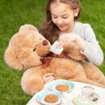 Smiling girl giving tea to plush bear — Stock Photo #50941999