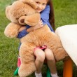 Girl hugging big teddy bear while sitting on chair at yard — Stock Photo #50942083