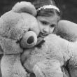 Monochrome portrait of small crying girl hugging teddy bear — Stock Photo #50942123