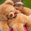 Photo of sad little girl hugging teddy bear — Stock Photo