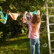Girl hanging clothes on clothesline at garden — Stock Photo #50944179