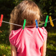 Girl being hanged by shirt on clothesline — Stock Photo #50944207