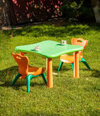 Toy plastic chair and table on grass at yard — Stock Photo