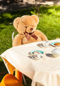 Teddy bear sitting behind table and drinking tea — Stock Photo