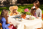 Little sisters having english breakfast with teddy bear at yard — Stock Photo