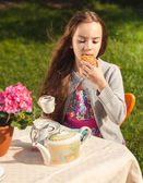 Beautiful girl having breakfast at yard and biting cookie — Stock Photo