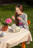 Girl having breakfast at yard and laughing loud — Stock Photo