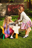 Cute girls having tea party at yard  — Stock Photo