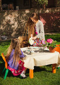 Girl pouring tea to her sister at toy tea party — Stockfoto