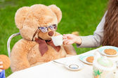 Girl giving tea to teddy bear at yard — Stock Photo