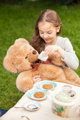 Smiling girl giving tea to plush bear — Stock Photo