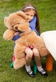 Girl hugging big teddy bear while sitting on chair at yard — Stock Photo