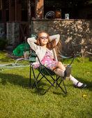 Cute girl in sunglasses sunbathing at backyard — Stock Photo