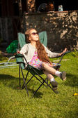 Young girl relaxing in armchair on grass at sunny day — Stock Photo