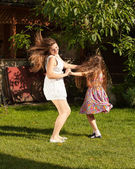 Mother and daughter dancing on grass at sunny day — Stock Photo