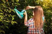 Woman in shirt drying bikini on clothesline — Stock Photo
