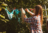 Beautiful woman drying swimsuits on clothesline — Stockfoto
