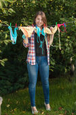 Woman hanging swimsuits on clothesline at garden — Stockfoto