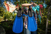 Woman drying flippers and snorkeling mask on clothesline — Stockfoto