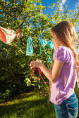 Photo of young girl drying clothes on clothesline — Foto Stock