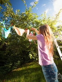 girl doing laundry and drying clothes at garden — Stock Photo