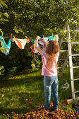 Girl hanging clothes on clothesline at garden — ストック写真