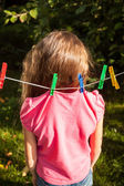 Girl being hanged by shirt on clothesline — ストック写真