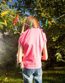 Little girl hanged by clothespins on rope — Stock Photo